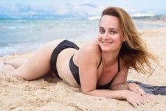 放松在海滩的泳装的美丽的妇女 免版税库存照片
