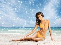 放松在海滩的泳装的美丽的妇女 免版税图库摄影