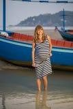 放松在海滩的美丽的孕妇 免版税库存照片