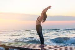 放松在海滩的被启迪的少妇,思考在asana hasta uttanasana,用在Namaste姿态的手在 免版税库存图片