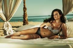 放松在海滩的逗人喜爱的深色的夫人。 库存图片