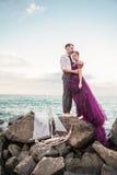 放松在海滩的年轻浪漫夫妇观看日落 免版税图库摄影
