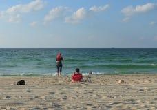 放松在海滩的年轻阿拉伯夫妇在一个晴朗的夏日 库存照片