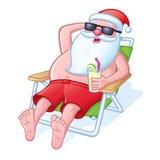 放松在海滩睡椅的圣诞老人 图库摄影