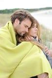 放松在温暖的衣物的海滩的有吸引力的夫妇在一明亮,但是凉快的天 图库摄影