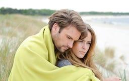 放松在温暖的衣物的海滩的有吸引力的夫妇在一明亮,但是凉快的天 免版税库存图片