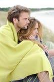 放松在温暖的衣物的海滩的有吸引力的夫妇在一明亮,但是凉快的天 库存照片