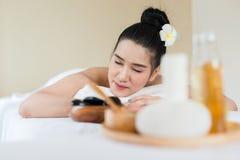 放松在温泉按摩的年轻美丽的亚裔妇女 图库摄影