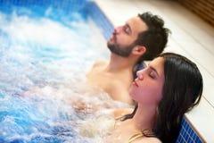 放松在温泉极可意浴缸的夫妇 库存图片