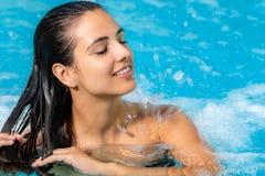 放松在温泉极可意浴缸的妇女 免版税库存图片