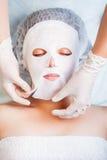 放松在温泉沙龙的妇女应用白色面罩 免版税图库摄影