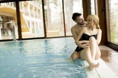 放松在温泉的爱恋的夫妇由水池 免版税库存图片