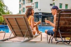 放松在游泳场旁边的不同种族的夫妇 库存图片
