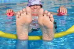 放松在游泳场的妇女,保持凉快 免版税库存照片