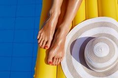 放松在游泳场的比基尼泳装的美丽的被晒黑的妇女画象  r 胶凝体波兰红色修脚 r 免版税库存图片