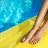 放松在游泳场的美丽的被晒黑的妇女画象  腿和手关闭  创造性的胶凝体波兰红色修脚和 免版税库存照片
