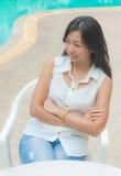 放松在游泳池旁边的一把椅子的一名亚裔妇女 免版税库存照片