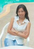 放松在游泳池旁边的一把椅子的一名亚裔妇女 库存图片