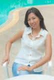 放松在游泳池旁边的一把椅子的一名亚裔妇女 免版税图库摄影