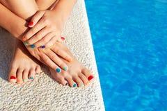 放松在游泳池旁边的女孩享用太阳在晴朗的夏天 免版税图库摄影
