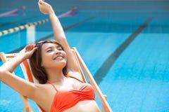 放松在游泳池旁边的椅子的少妇 免版税库存图片