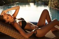 放松在游泳池旁边的黑比基尼泳装的性感的白肤金发的女孩 库存照片