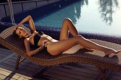 放松在游泳池旁边的黑比基尼泳装的性感的白肤金发的女孩 免版税库存照片