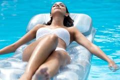 放松在游泳池的俏丽的女孩夏令时 免版税库存图片