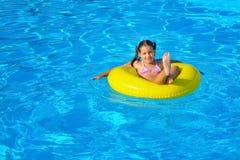 放松在游泳池的可爱的小孩 库存照片