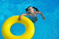 放松在游泳池的可爱的小孩 免版税库存图片
