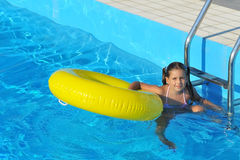 放松在游泳池的可爱的小孩 免版税库存照片