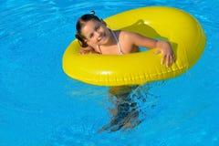 放松在游泳池的可爱的小孩 免版税图库摄影