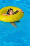 放松在游泳池的可爱的小孩 库存图片
