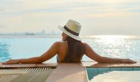 放松在游泳池的大帽子的妇女,在海附近 库存图片
