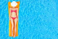 放松在游泳池的女性秀丽 免版税库存照片