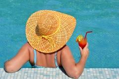 放松在游泳池的实际女性秀丽 免版税库存图片