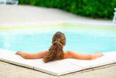 放松在游泳池的少妇 查出的背面图白色 免版税图库摄影