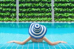 放松在游泳池的年轻亚裔妇女在温泉渡假胜地 放松的概念 妇女是松弛在游泳池边 免版税库存图片