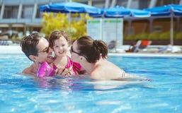 放松在游泳池的快乐的家庭 库存图片