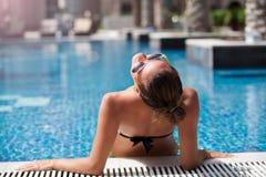 放松在游泳池的暑假无忧无虑的妇女 免版税库存照片