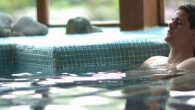 放松在游泳池的有吸引力的夫妇 股票录像