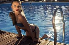 放松在游泳池的比基尼泳装的性感的美丽的女孩 免版税库存照片