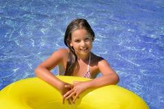 放松在游泳池的真正的可爱的女孩 库存照片