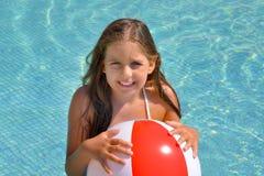 放松在游泳池的真正的可爱的女孩 免版税库存图片