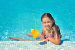 放松在游泳池的真正的可爱的女孩 免版税库存照片
