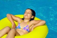 放松在游泳池的真正的可爱的女孩 免版税图库摄影