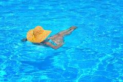 放松在游泳池的真正的女性秀丽 图库摄影