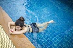 放松在游泳池的美丽的妇女 免版税库存照片