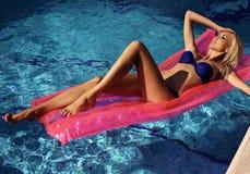 放松在游泳池的蓝色比基尼泳装的性感的白肤金发的妇女 库存图片