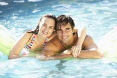 放松在游泳池的年轻夫妇画象  库存图片